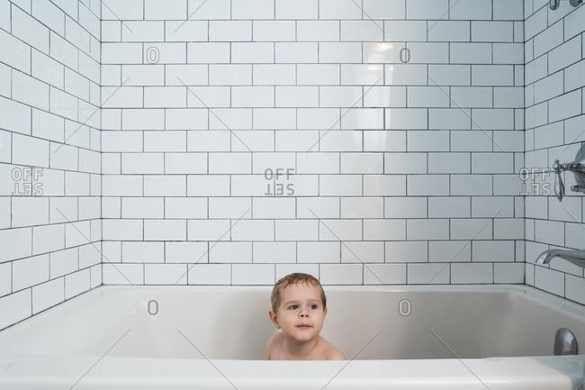 Child taking a bath in a modern tied tub