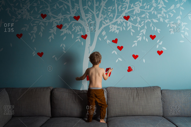 Toddler decorating a wall decal of a tree with red hearts for valentines day
