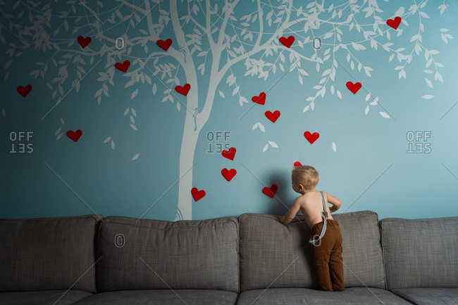 Cute toddler decorating a wall decal of a tree with red hearts for valentines day
