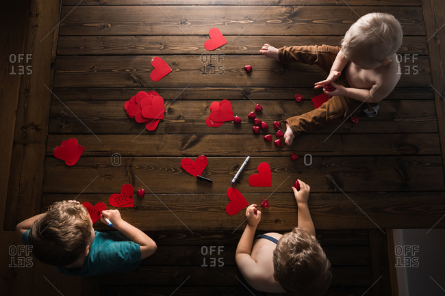 Overhead view of three young boys creating valentines day decorations