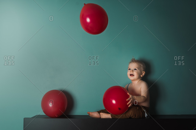 Cute baby boy tossing red balloons in bedroom