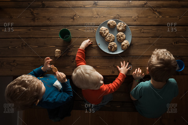 Overhead view of three boys sharing a plate of cookies at the table