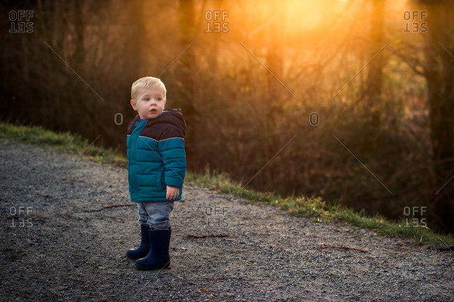 Adorable toddler in winter jacket on a sunset hike