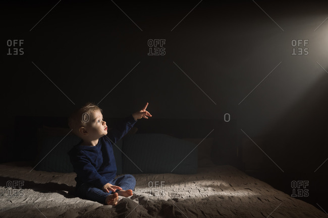Baby boy pointing towards dramatic light falling from window