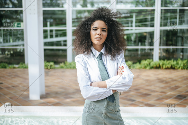 Spain, Madrid, portrait of woman with afro hair and tie with crossed arms, looking at camera