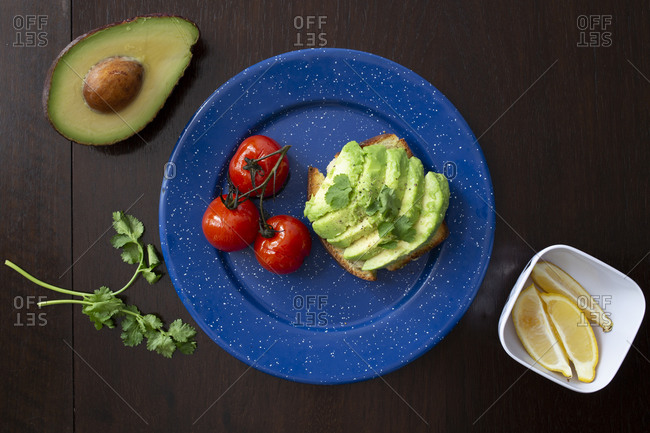 A breakfast of Avocado toast with grilled tomatoes, lemon and fresh parsley