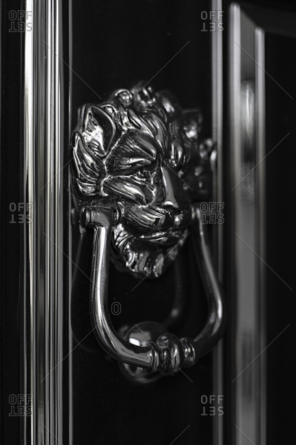 Closeup of shiny lion door knocker, black and white