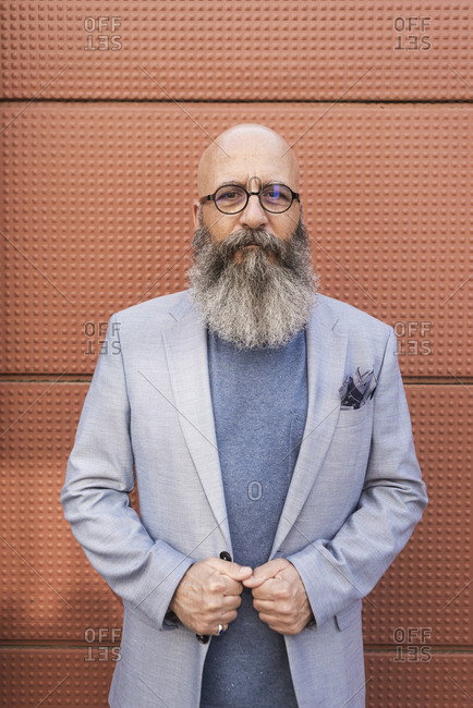 Portrait of a hipster bearded mature man wearing blue jacket and eyeglasses outdoors