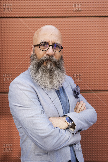 Portrait of a hipster bearded mature man wearing blue jacket and eyeglasses arms crossed outdoors