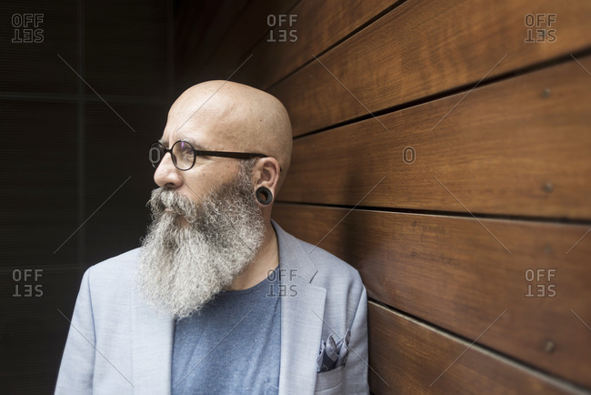 Portrait of a hipster bearded mature man wearing blue jacket and eyeglasses leaning on a wall