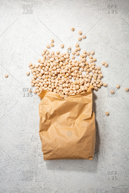 Overhead view of chickpeas spilling out of paper bag
