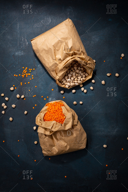 Overhead view of chickpeas and red lentils in paper bags