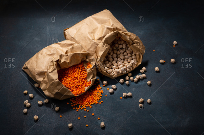 Chickpeas and red lentils in paper bags  on dark surface