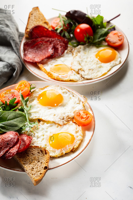 Close up of breakfast eggs with salami and salad
