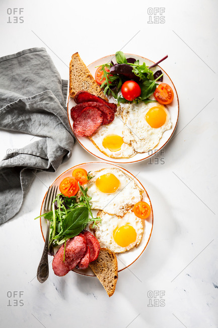 Overhead view of two plates with fried eggs and salami
