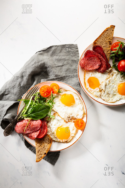 Overhead view of two plates with fried eggs and salami on light surface