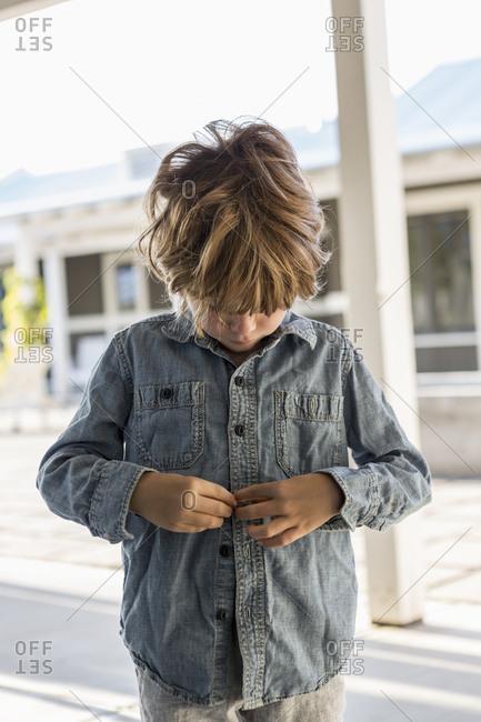 A young boy buttoning up his denim shirt
