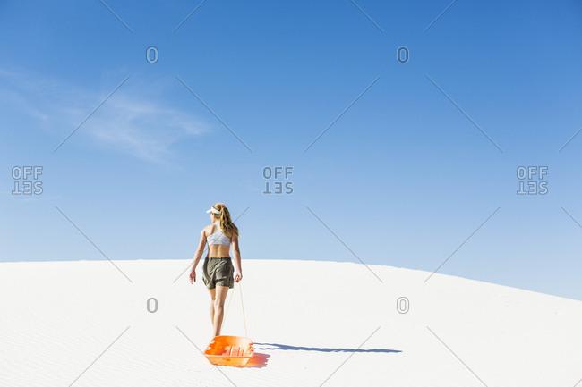 A teenage girl pulling a sled