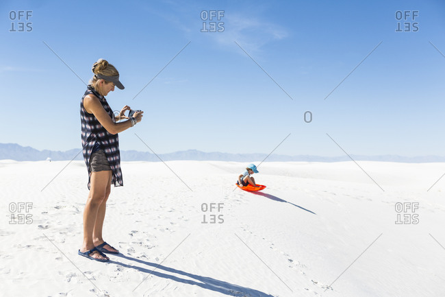 Mother taking picture of son sledding on sand dunes