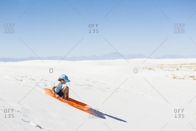A young boy sledding on sand dune