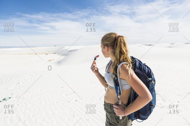 A teenage girl hiking across white sand dunes