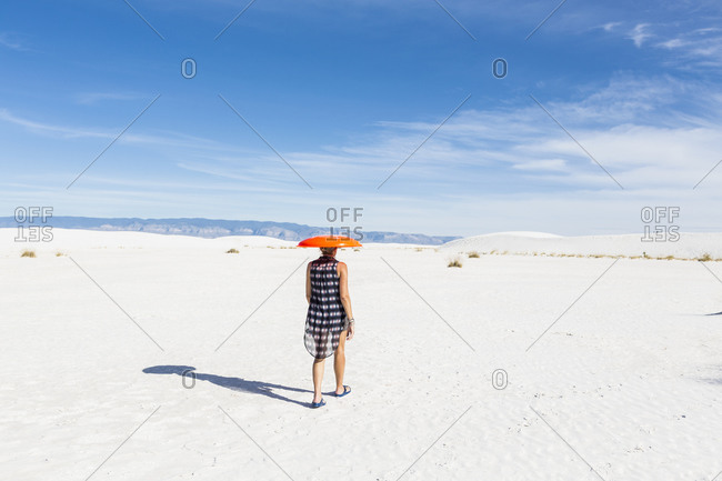 Woman carrying orange sled on her head.