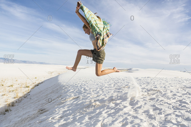 A teenage girl leaping in the air, in a wide open space, sand dunes.