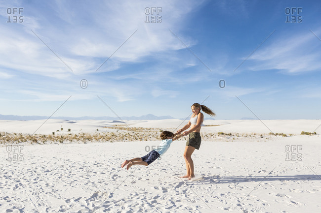 A teenage girl swinging her 6 year old brother in sand,