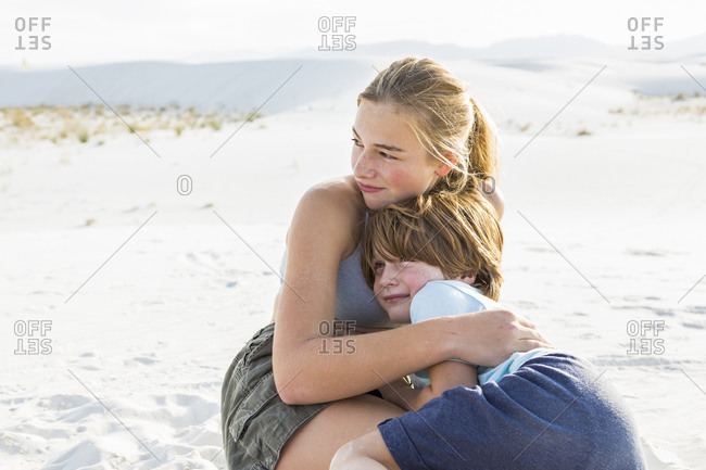 A teenage girl embracing her brother,