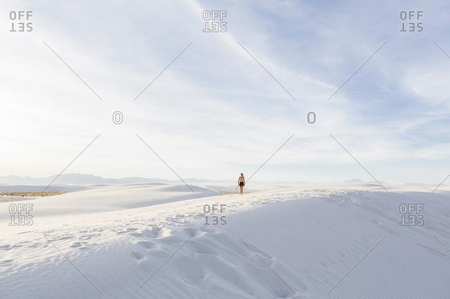 Woman walking in white sand dunes