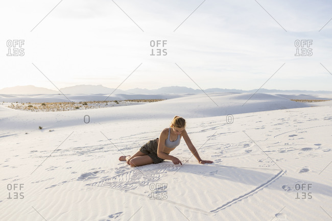 A teenage girl drawing in the sand,