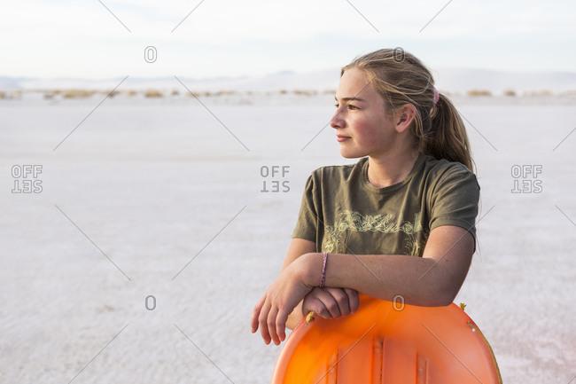 A teenage girl leaning on orange sled,