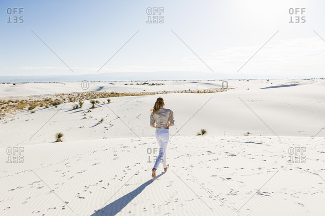 A teenage girl standing looking at a vast open space of sand dunes.