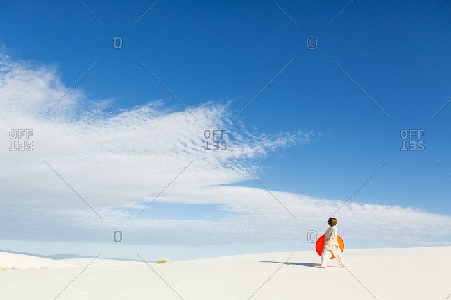 A young boy carrying an orange sled in a white undulating dune landscape.
