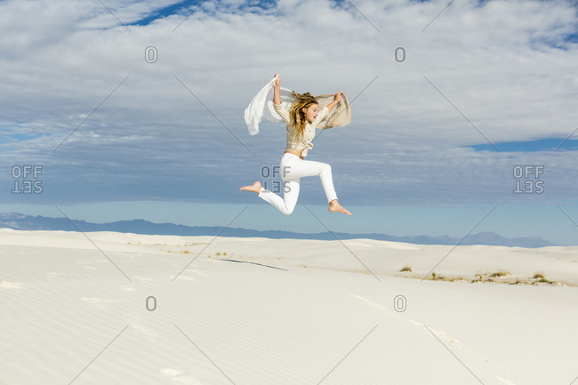 A teenage girl dancing and leaping n mid air in the open space on white sand dunes