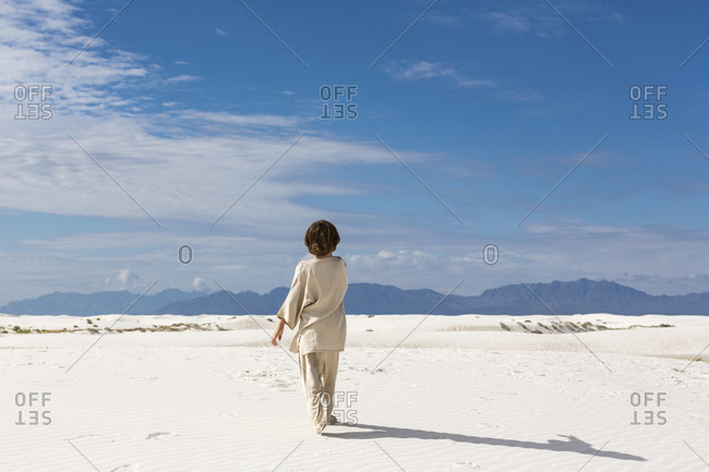 A young boy walking in sand dunes.