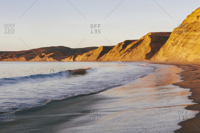 Steep cliffs and beach with surf at dawn