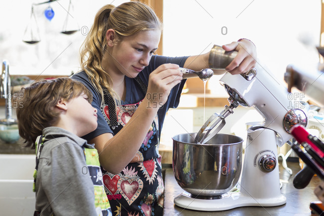 A teenage girl and her 6 year old brother in a kitchen, using a mixing bowl