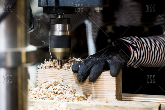 Close up of person wearing protective gloves using electric drill in wood workshop.