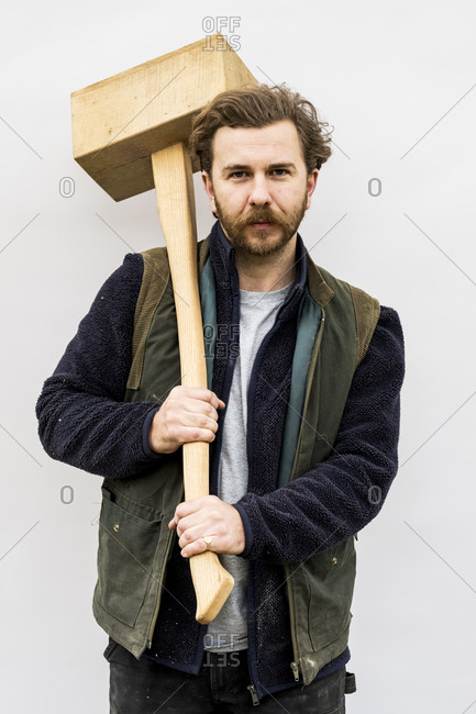 Portrait of bearded man holding wooden block standing in front of white background, looking at camera.