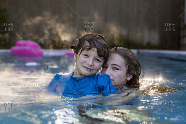 A boy and girl playing in pool in early morning light