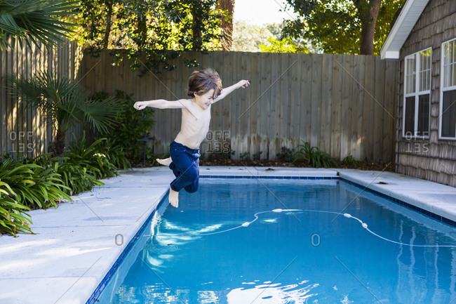 A six year old boy leaping into a swimming pool