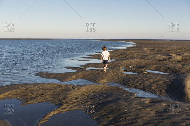 A six year old boy investigating sandy landscape