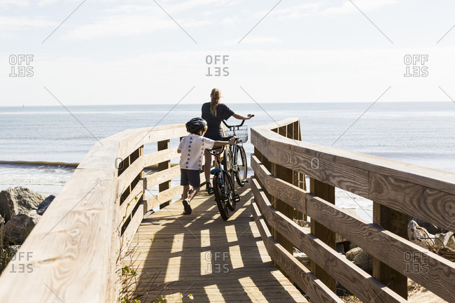 Two children, brother and sister on wooden bridge with bikes