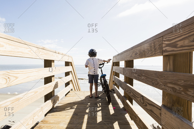 A young boy on wooden bridge with his bike