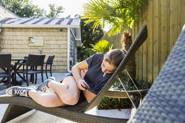 A teenage girl lying in a sun lounger checking her phone