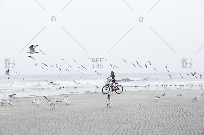 A teenage girl biking on a sandy beach by the ocean