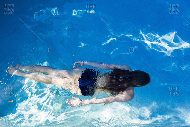 A teenage girl swimming in a pool, view from above.