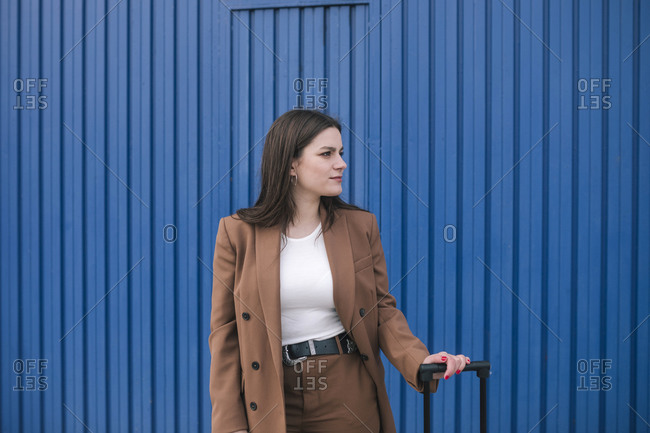 Young woman in a blazer waiting with her suitcase