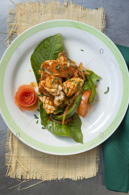 Plate of seafood in Indonesian tradition with flower shaped vegetable
